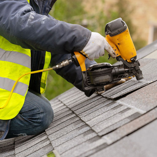 Construction worker nailing down roofing